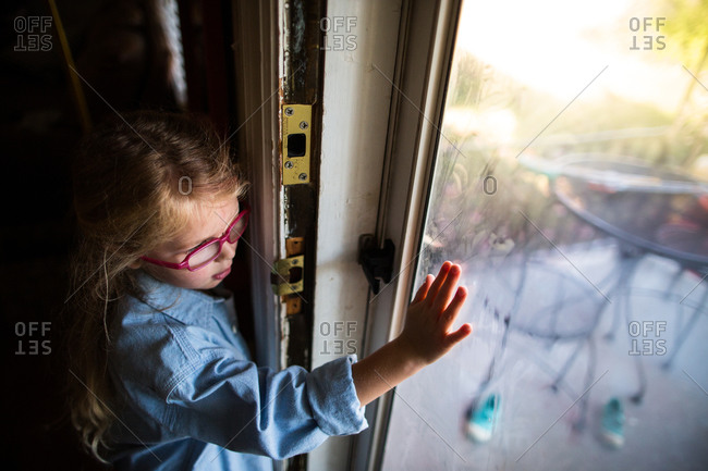 Girl with glasses looking out glass door