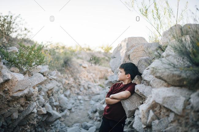 A boy leans back in a rocky ditch