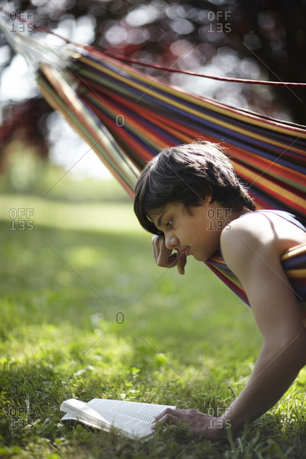 Boy reading off edge of hammock
