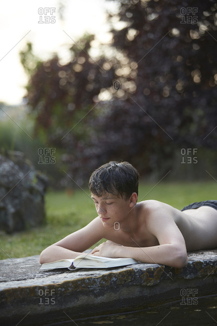 Adolescent boy reading on edge of stone pool