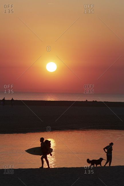 People silhouetted on beach at sunset