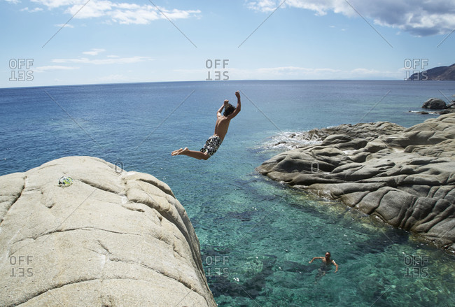 Boy jumping off rock into crystal clear sea
