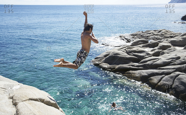 Cliff jumping into blue waters