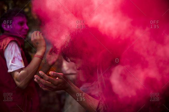 Mathura, India - March 13, 2014: Red gulal thrown out at a man during Holi Festival