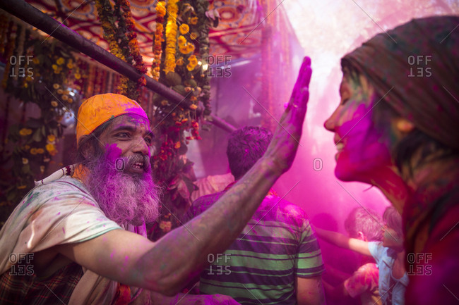 Mathura, India - March 13, 2014: Man putting pink gulal on a tourist's face during Holi