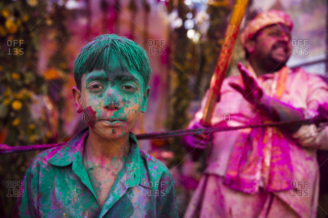 Mathura, India - March 13, 2014: Boy covered with green gulal during Holi Festival