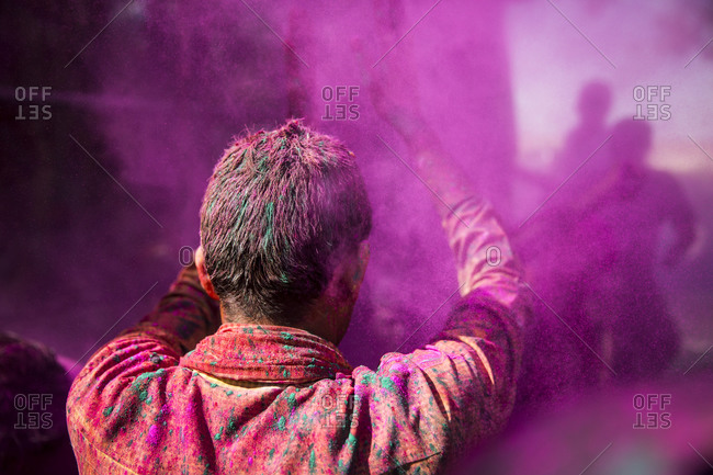 Man dancing in a cloud of pink gulal during Holi, Mathura, India