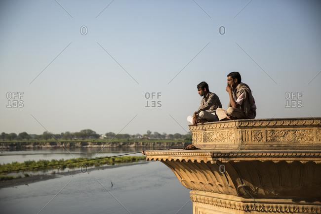 Vrindavan, India - March 15, 2014: Men sitting at a platform by the river Yamuna