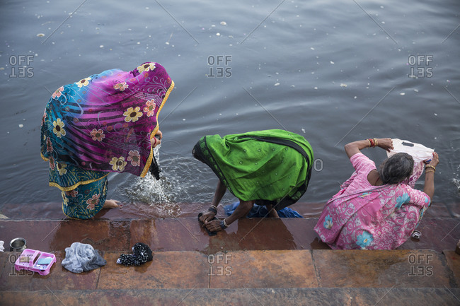 Women washing clothes by the Yamuna river, India