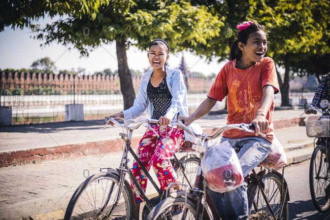 Mandalay, Myanmar - December 23, 2012: Three female friends laughing on bikes