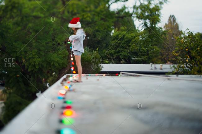Young girl placing Christmas lights on a rooftop