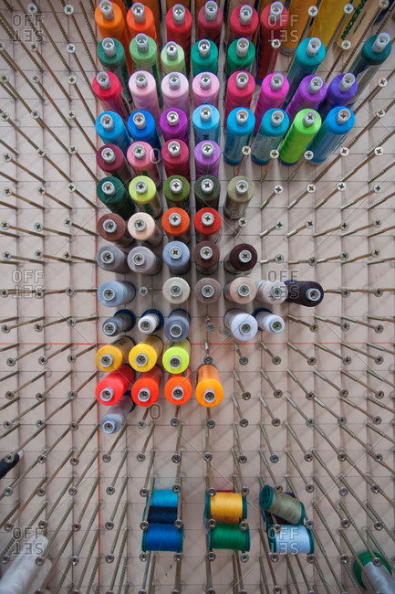 Spools of thread hanging on a wall