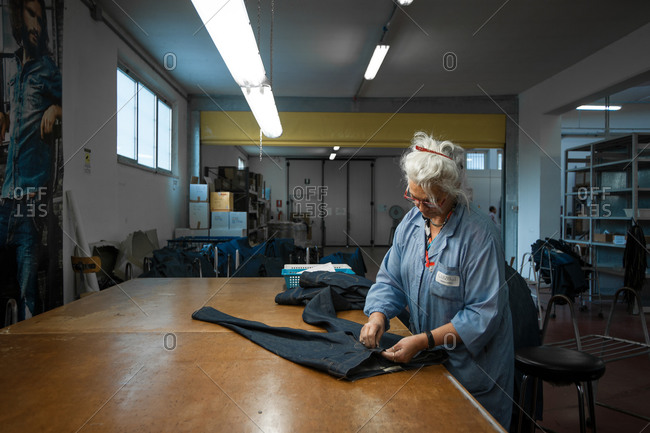 Pesaro-Urbino Province, Italy - October 31, 2014: Senior woman working in apparel manufacturing workshop