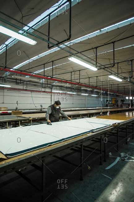 Pesaro-Urbino Province, Italy - October 31, 2014: Man working with a large piece of fabric