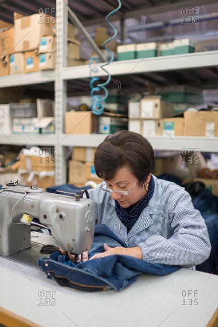 Pesaro-Urbino Province, Italy - October 31, 2014: Senior woman working on sewing machine