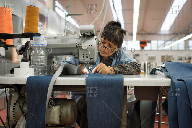 Pesaro-Urbino Province, Italy - October 31, 2014: Woman sewing pants on sewing machine