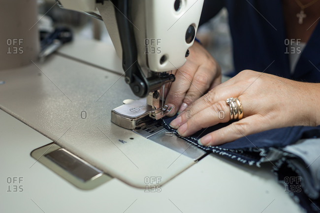 Close up of woman sewing jeans
