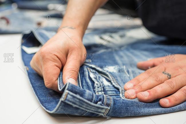 Man smoothing out denim pants