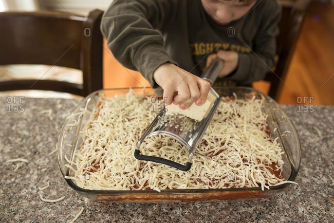 Young boy grating cheese on a lasagna