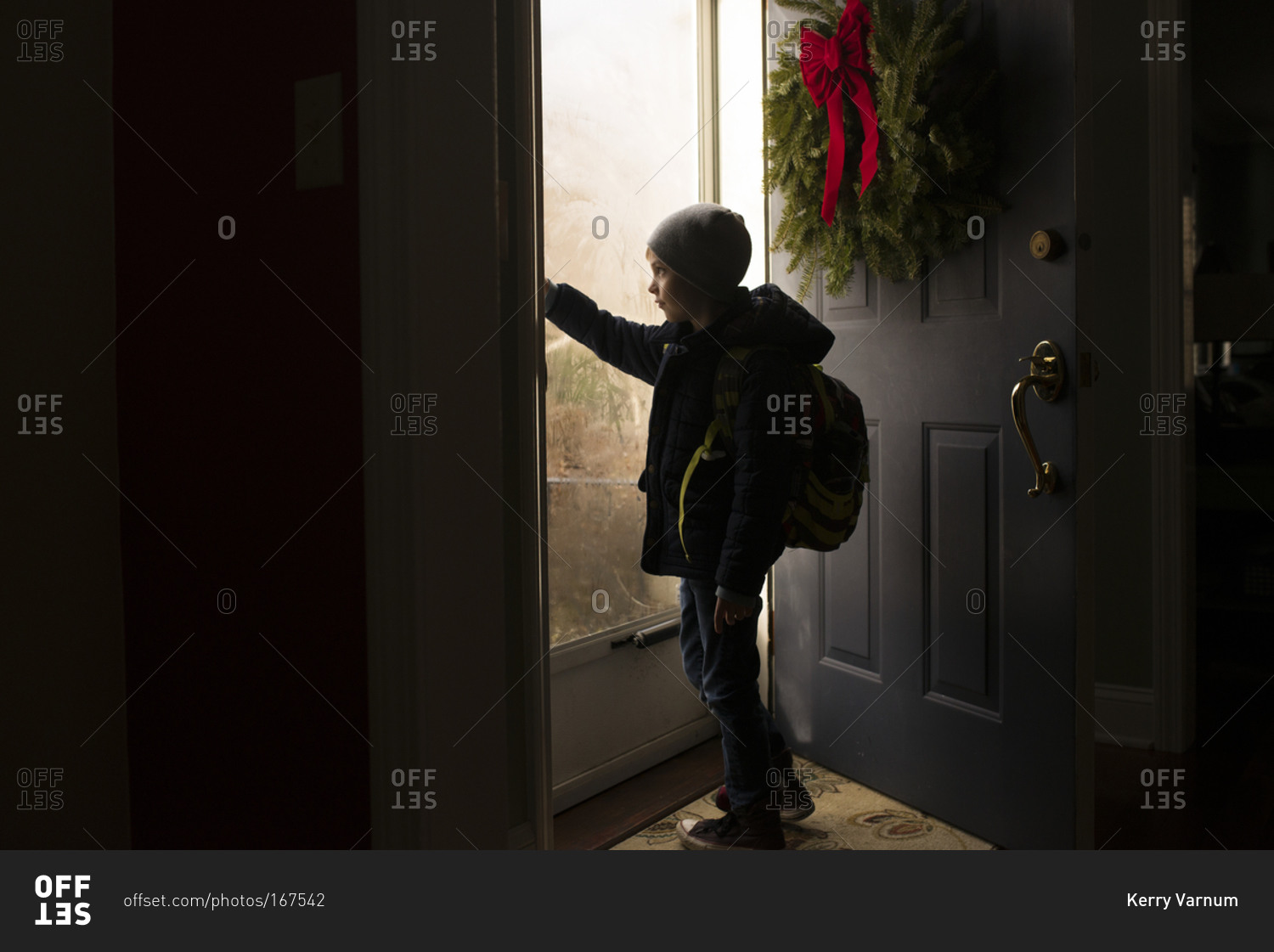 Young boy opening the front door & Young boy opening the front door stock photo - OFFSET