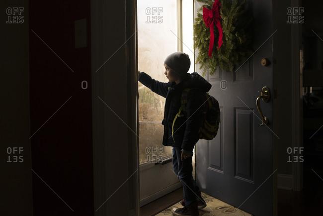 Young boy opening the front door