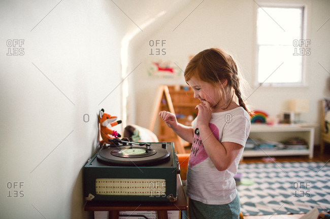 Young girl playing record on a record player