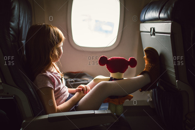 Young girl with her doll on an airplane