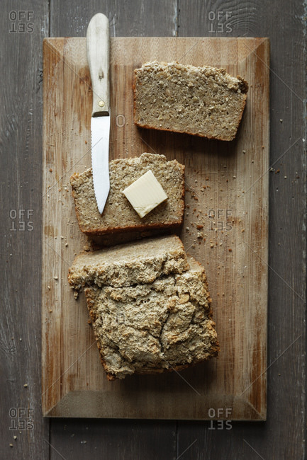 Piece of butter and kitchen knife wooden board