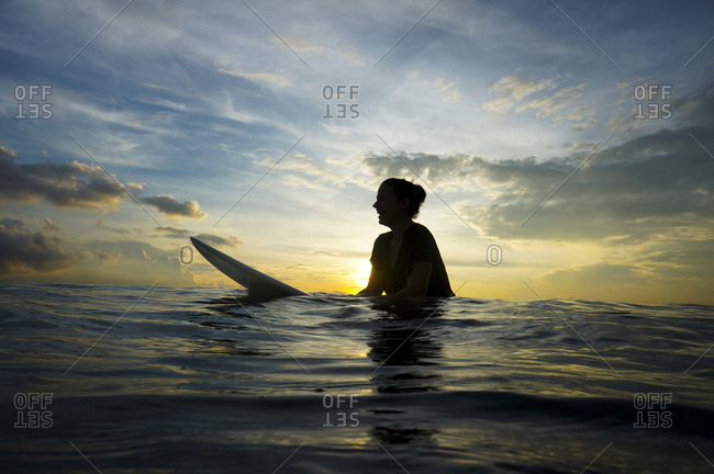 Silhouette of young woman with surfboard by twilight, Bali