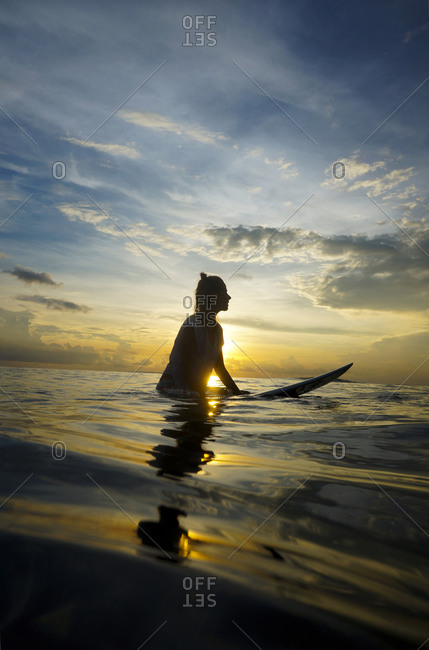 Silhouette of female surfer by twilight, Bali