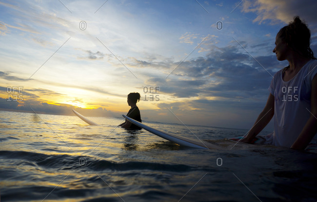 Two female surfer in the water watching sun, Bali