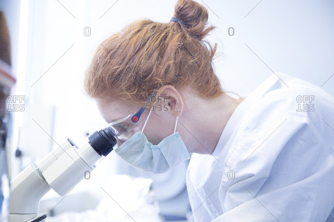 Young female natural scientist looking through microscope in biochemistry laboratory
