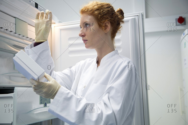 Young female natural scientist controlling a test in biochemistry laboratory
