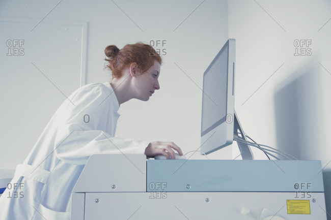 Young female natural scientist working at computer in biochemistry laboratory