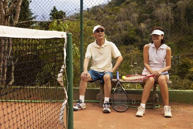 Senior couple resting on a bench at a tennis court