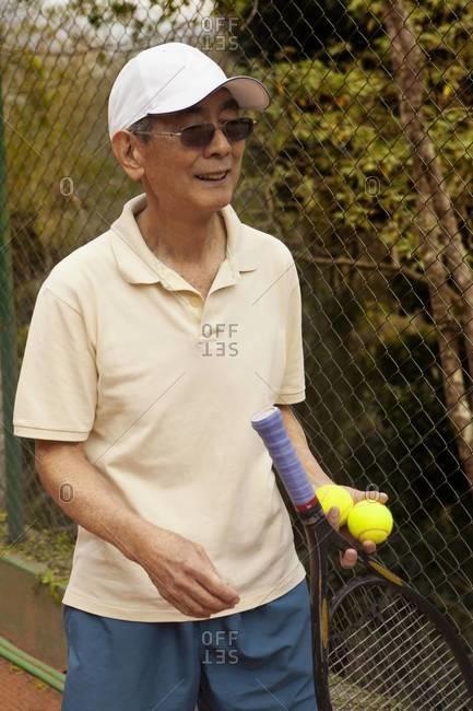 Portrait of senior man with tennis racket