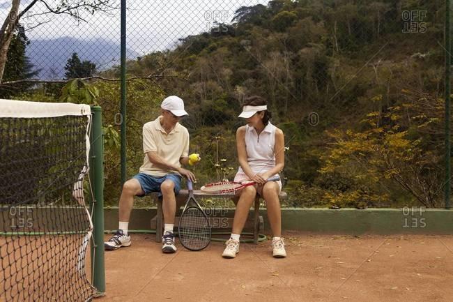 Senior couple sitting on a bench at a tennis court
