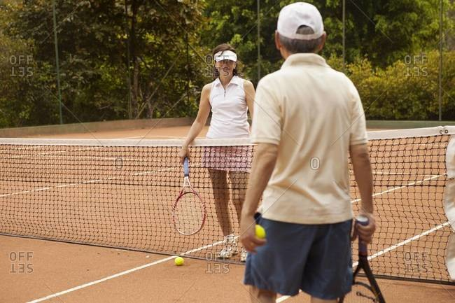 Senior couple talking by the net at a tennis court
