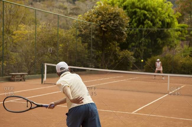 Husband and wife playing tennis