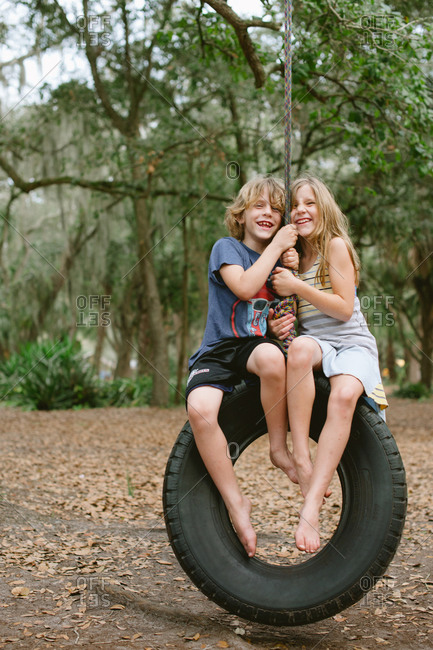 Boy and girl on a tire swing