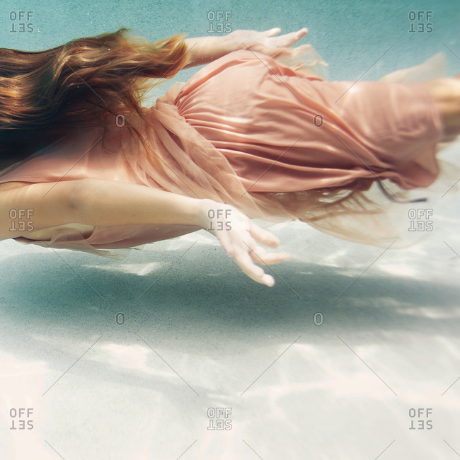 Girl swimming in a dress underwater