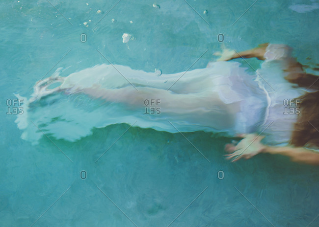 Girl swimming in a pool dressed up