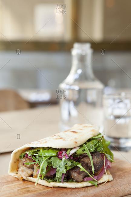 Flatbread sandwich with beef, pork and arugula