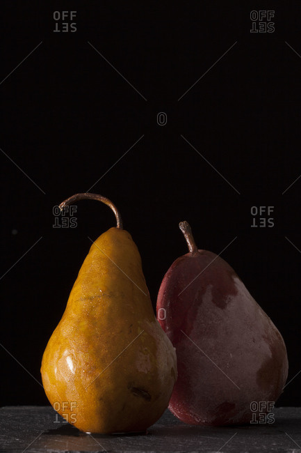 Two frosty pears on black background