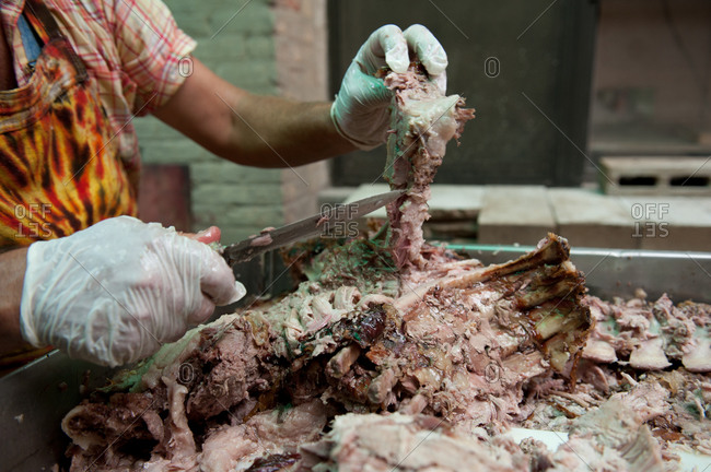 Chef cutting the meat off a roasted pig