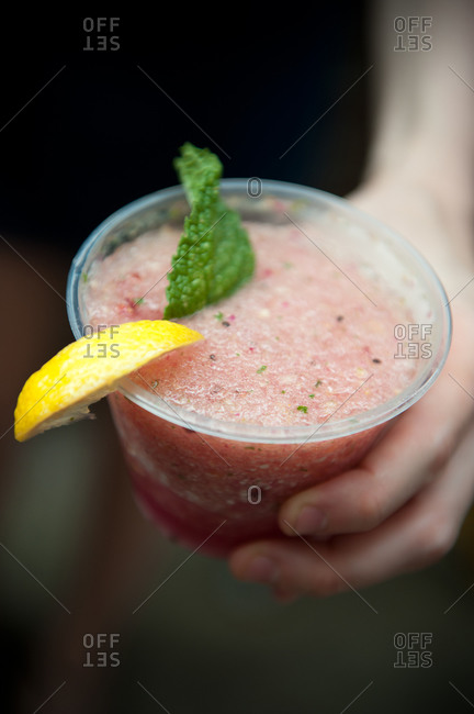 Hand holding a frozen drink with lemon and mint