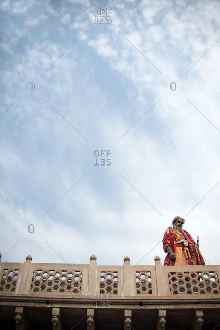 Nandgaon, India - March 10, 2014: Sadhu standing on a roof in Nandgaon, India