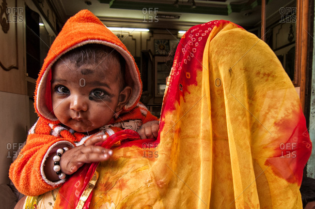 Rajasthan, India - March 7, 2014: Mother holding a baby with painted eyes