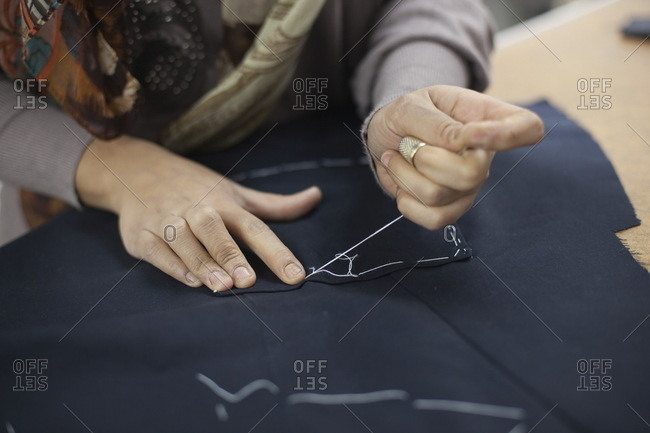 A woman sewing a pocket on a tailoring jacket