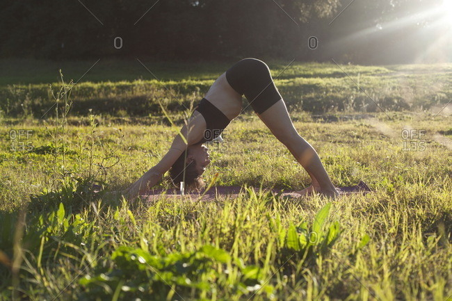 A woman practicing yoga in a park